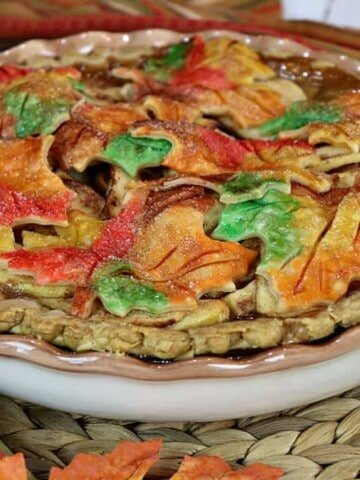 A colorful autumn leaves apple pie on a rattan place mat surrounded by fall leaves.