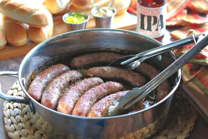 A large skillet of beer braised bratwurst with a pair of tongs. Buns and beer are in the background.