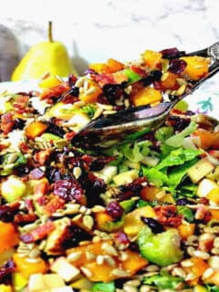 A closeup horizontal photo of salad tongs in a large bowl of colorful fall chopped salad