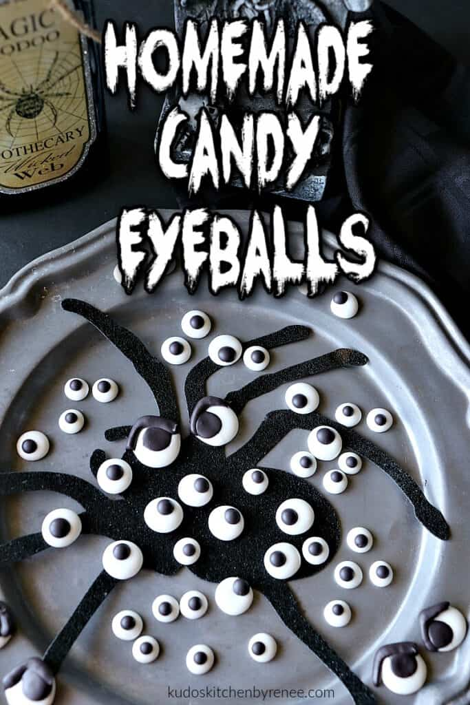 A vertical closeup photo of a bunch of Homemade Candy Eyeballs on a pewter plate with a scary looking title text overlay graphic.