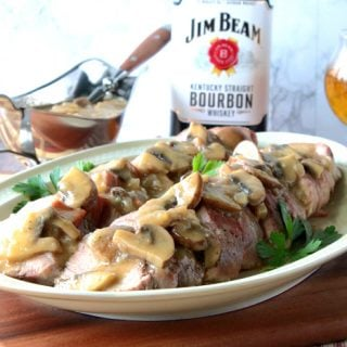 A sliced pork tenderloin on a platter with mushroom gravy and a glass of bourbon in the background.