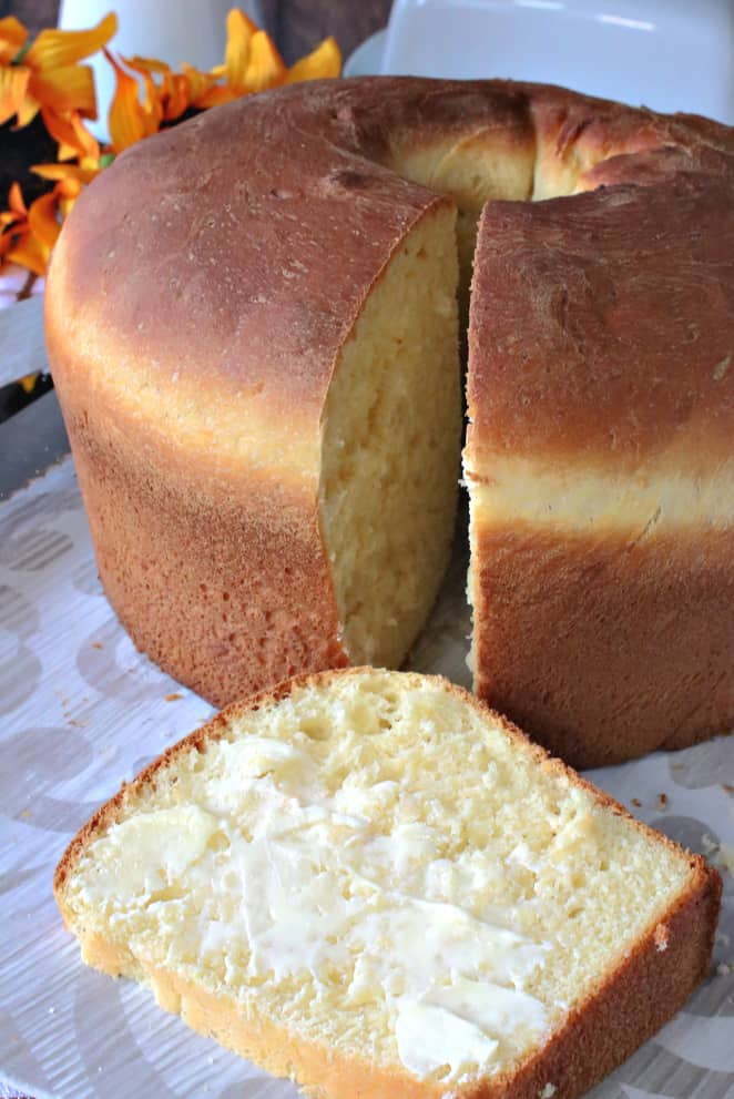 A vertical closeup picture of a slice of Sally Lunn enriched batter bread on a plate with butter.