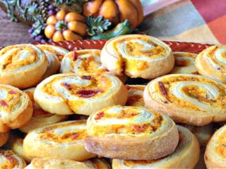 A pile of savory pumpkin pinwheel appetizers on a platter with a cornucopia in the background