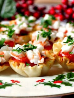 A festive plate filled with Shrimp Cocktail Appetizer Bites with red and green holiday accents.