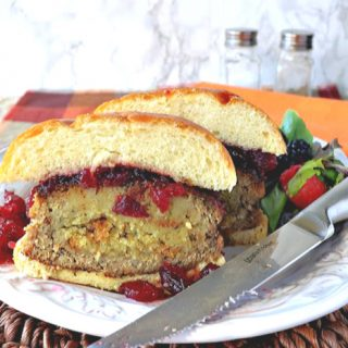 A turkey burger stuffed with stuffing cut in half on a plate with a knife of the side.