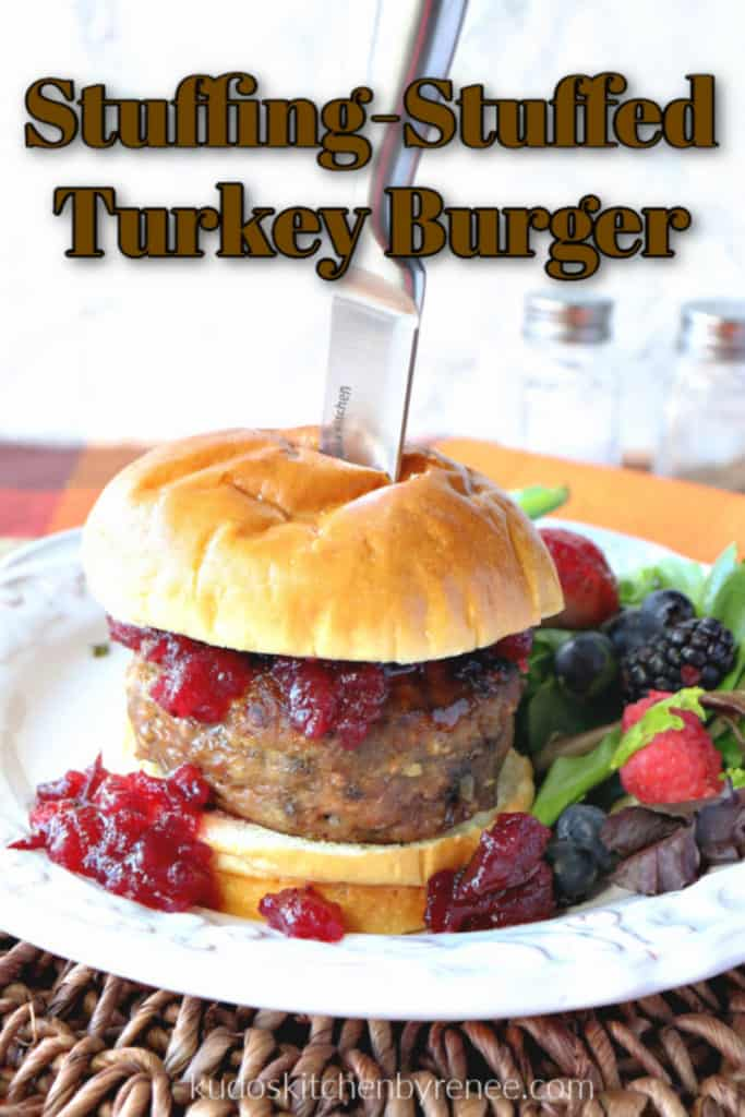 A vertical photo of a stuffing-stuffed turkey burger on a white plate topped with cranberry sauce and a knife with title text overlay graphic