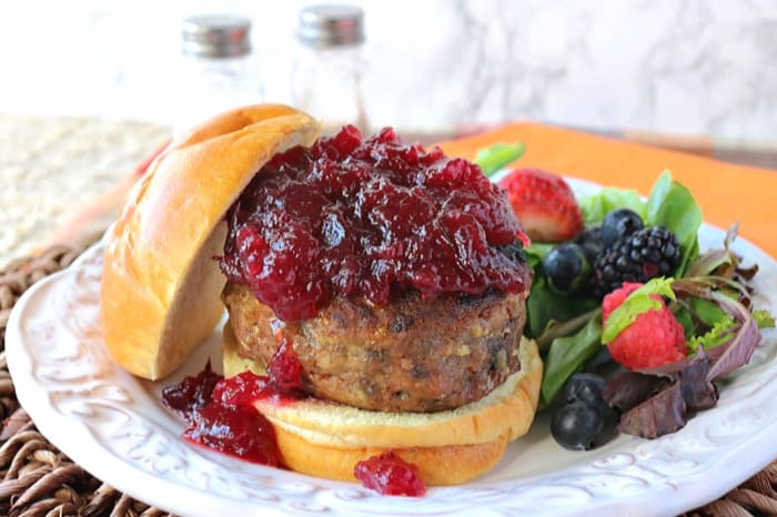 A horizontal photo of a turkey burger covered with cranberry sauce on a brioche bun.