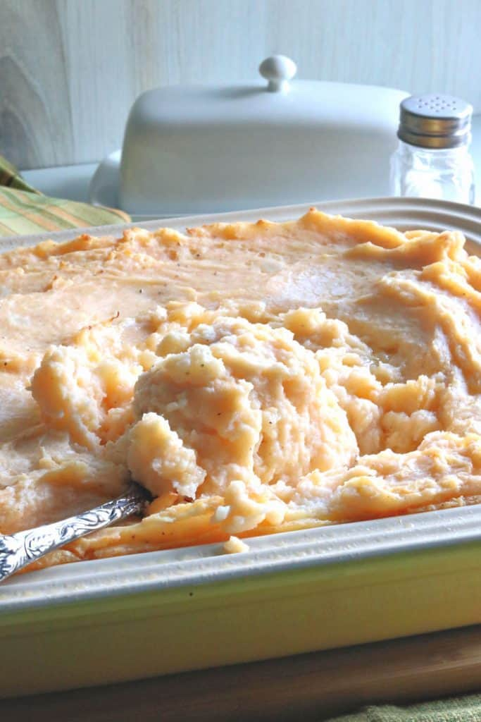 A casserole dish filled with cheese horseradish mashed potatoes with melted butter on top.