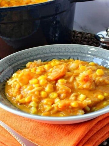 A blue bowl filled with pumpkin corn chowder with shrimp on an orange napkin with a spoon and salt and pepper shakers