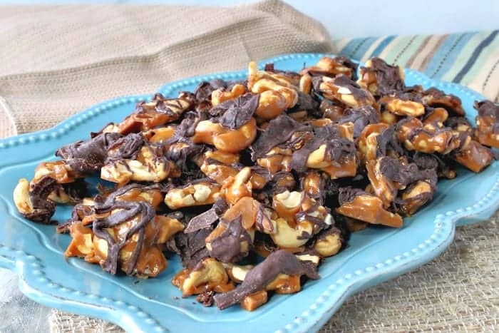 A blue plate fulled with butter toffee cashew clusters with chocolate.