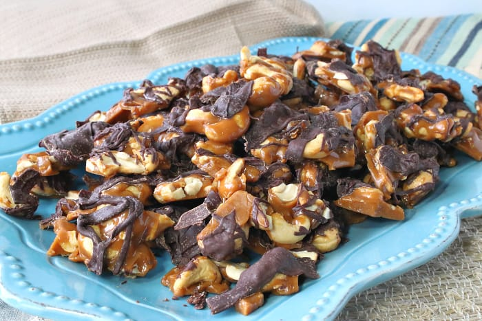 Horizontal photo of a platter of butter toffee cashew crunch with a chocolate drizzle and a blue and tan striped napkin.