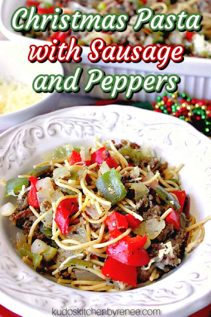 A vertical closeup of a pretty white bowl filled with Christmas Pasta with Sausage, Onion, and Peppers with a title text overlay graphic in red, white, and green