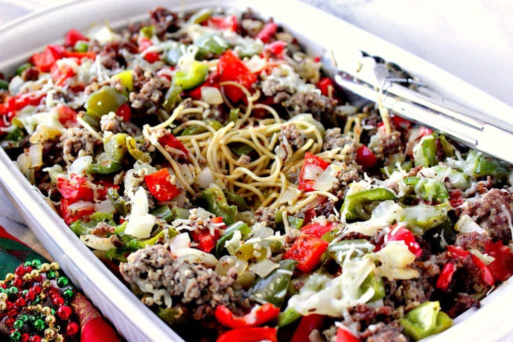 A horizontal closeup photo of spaghetti, sausage, and peppers in a casserole dish with tongs.