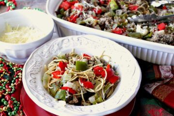 A festive looking bowl of Christmas pasta with red and green peppers in a pretty white bowl.