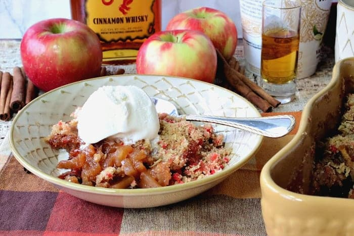 A bowl of fireball apple crisp with a scoop of vanilla ice cream and a spoon.