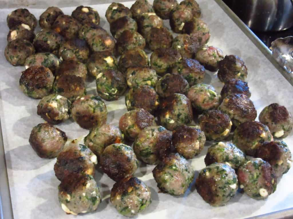 Greek meatballs on a baking sheet.