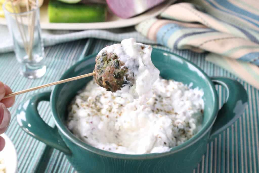 A Greek meatball appetizer on a toothpick with tzatziki sauce.