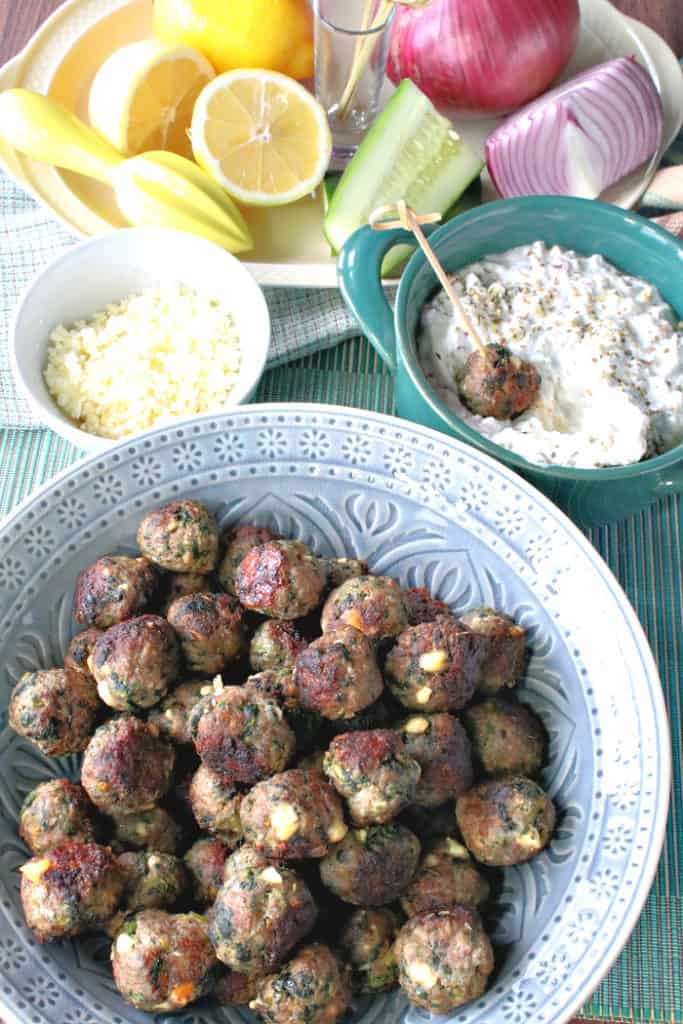 A vertical photo of a blue bowl of Greek appetizer meatballs with feta cheese, spinach, and tzatziki sauce.