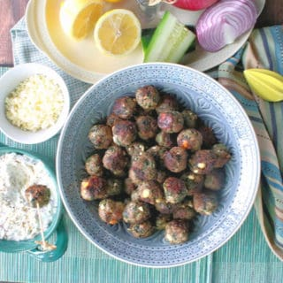 Overhead photo of a bowl of Greek meatball appetizers with sauce, feta cheese, lemons and cucumbers.