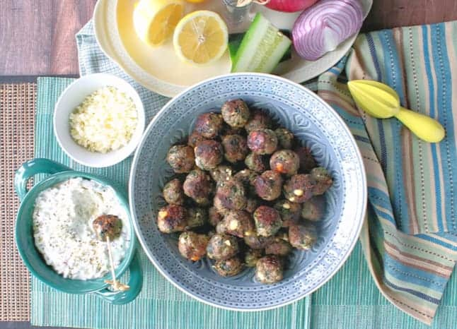 Overhead photo of a bowl of Greek appetizer meatballs with feta cheese and tzatziki sauce, cucumber, onion, and lemon.
