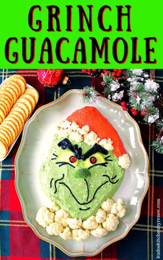 Highly saturated vertical title text image of Grinch guacamole with crackers and Christmas ornaments on a plaid tablecloth.