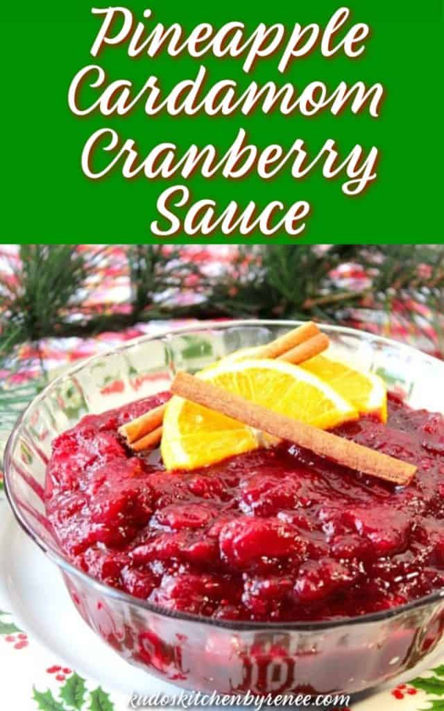 Vertical title text image of pineapple cardamom cranberry sauce in a glass bowl with cinnamon sticks and orange slices.