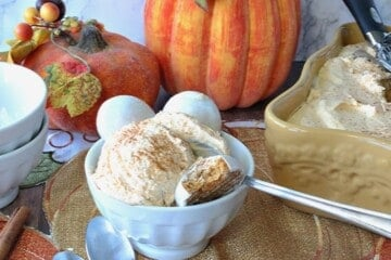 A small white bowl with a scoop of pumpkin pie ice cream, a spoon, and cookies.