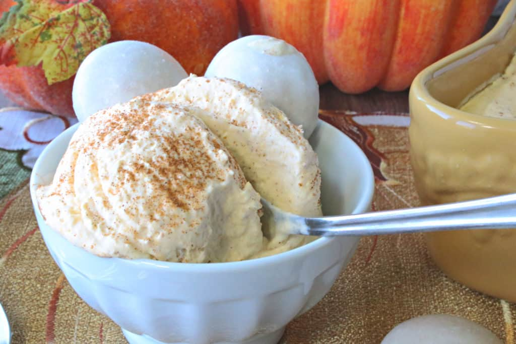 Closeup photo of a creamy dish of no churn pumpkin ice cream with cinnamon sprinkled on top and a spoon.