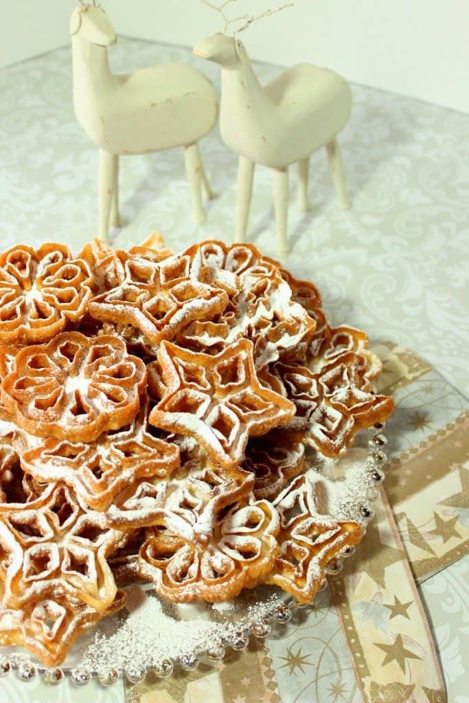 A vertical photo of a pile of rosette snowflake cookies on a glass plate with confectioners sugar and two white wooden deer in the background.