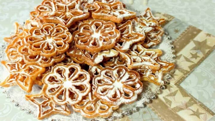 A round glass platter filled with rosette snowflake cookies with confectioners sugar dusting