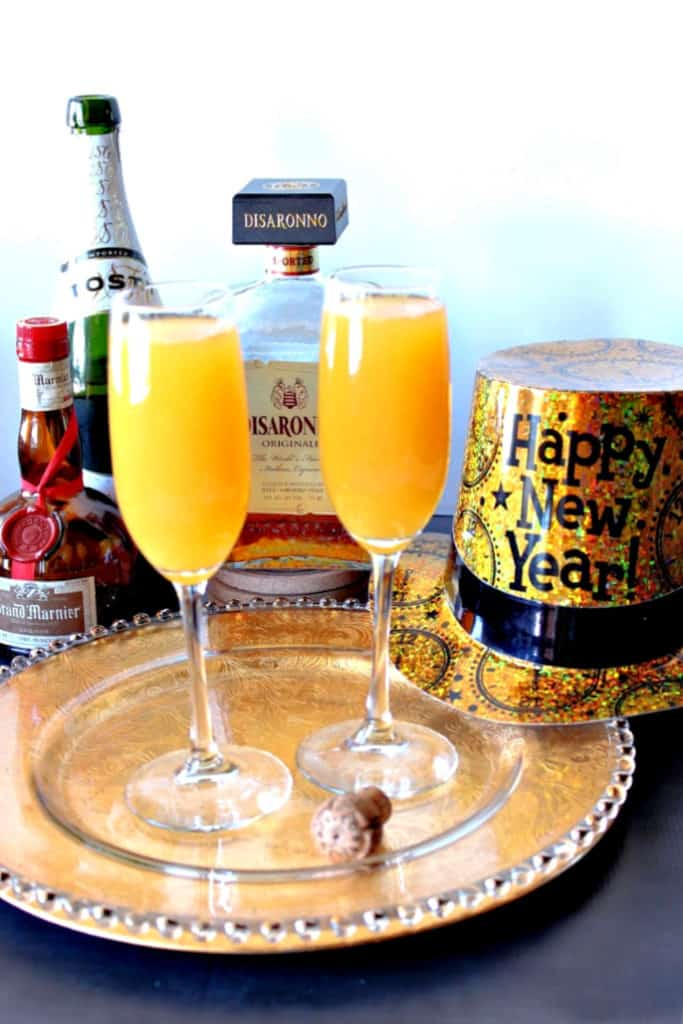 Two champagne glasses filled with the very best mimosas with amaretto, champagne and grand marnier in the background along with a new year's hat.