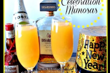 A closeup photo of two celebration mimosas in champagne glasses with a new years hat on the side.