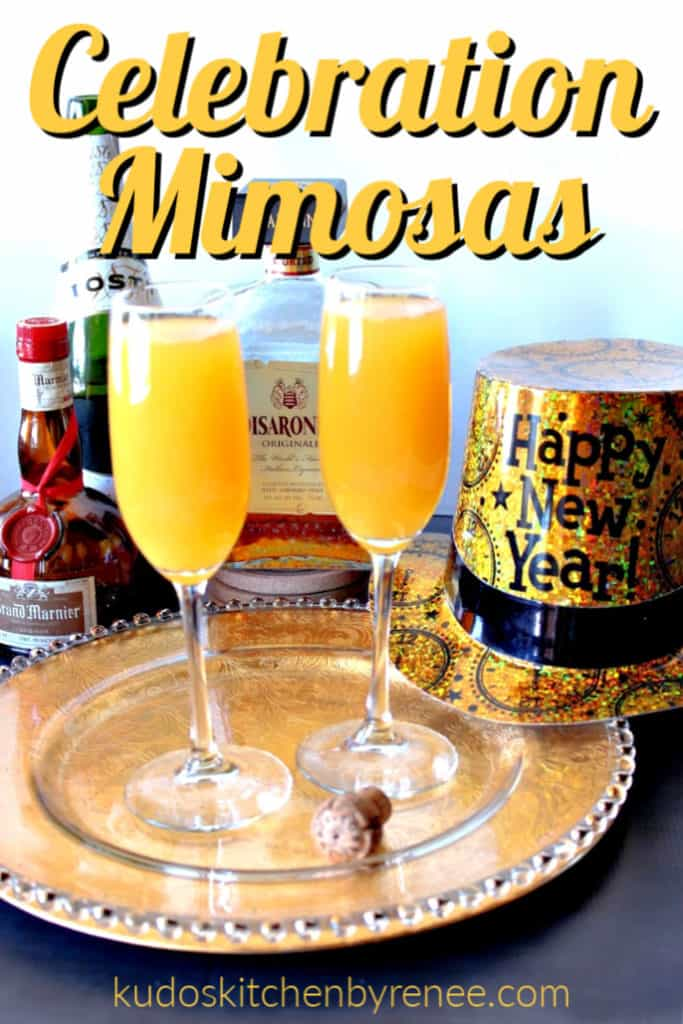 A vertical title text image of two mimosas on a decorative tray with a wine cork, a new years hat, and alcohol bottles in the background.