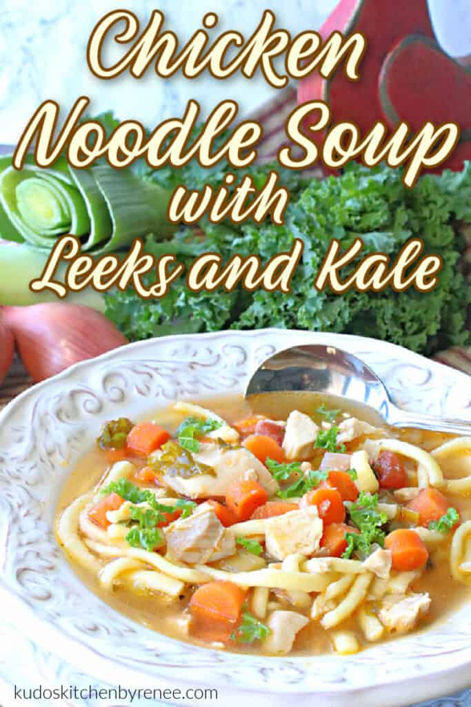 A vertical closeup photo of a white bowl filled with Chicken Noodle Soup with Leeks and Kale along with a title text overlay graphic