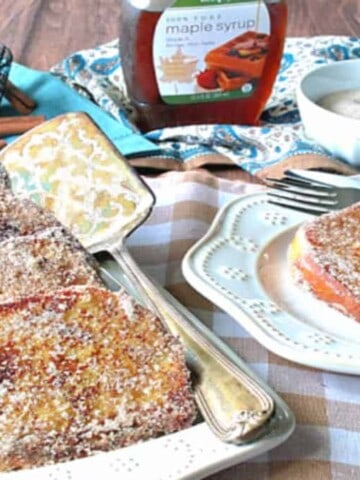 A table set up with breakfast of cinnamon sugar french toast with eggs and syrup in the background