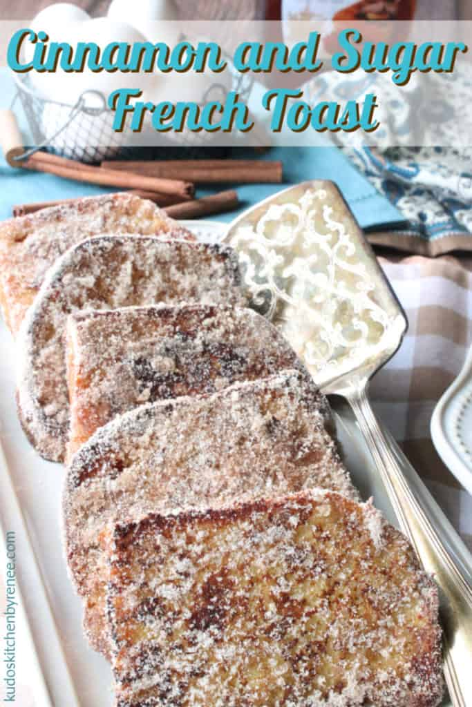 A vertical title text image of a rectangle tray filled to the brim with cinnamon and sugar French toast with cinnamon sticks in the background and a silver spatula on the platter.