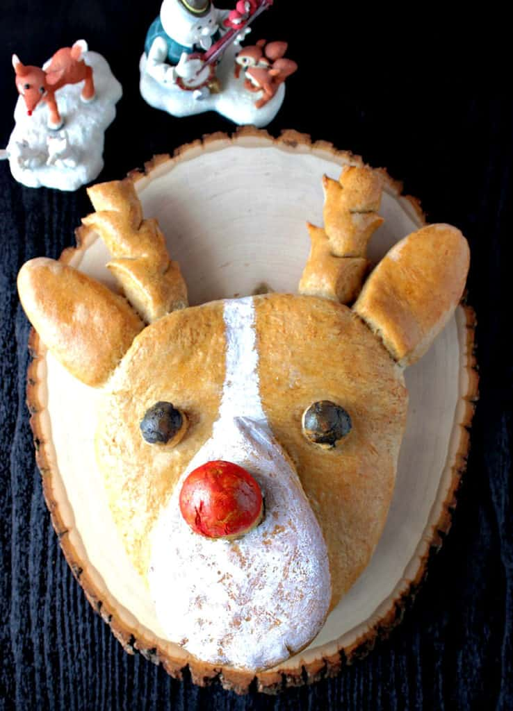 Vertical closeup overhead image of Rudolph bread with a red nose and antlers.