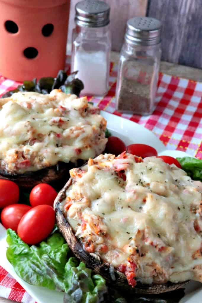 A vertical closeup photo of two chicken Parmesan stuffed portobello mushrooms on a plate with lettuce and grape tomatoes.