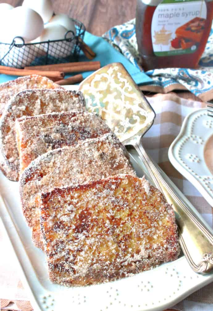 Vertical closeup image of a rectangle platter filled with cinnamon and sugar french toast with a basket of eggs in the background and a bottle of maple syrup.