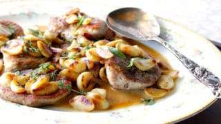 A platter filled with garlic lovers pork chops with whole garlic, sauce, fresh herbs and a serving spoon