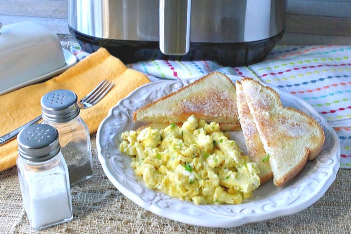 A white plate filled with air fryer scrambled eggs with chives. Toast and butter is on the side and salt and pepper shakers are in the foreground while and air fryer is in the background.