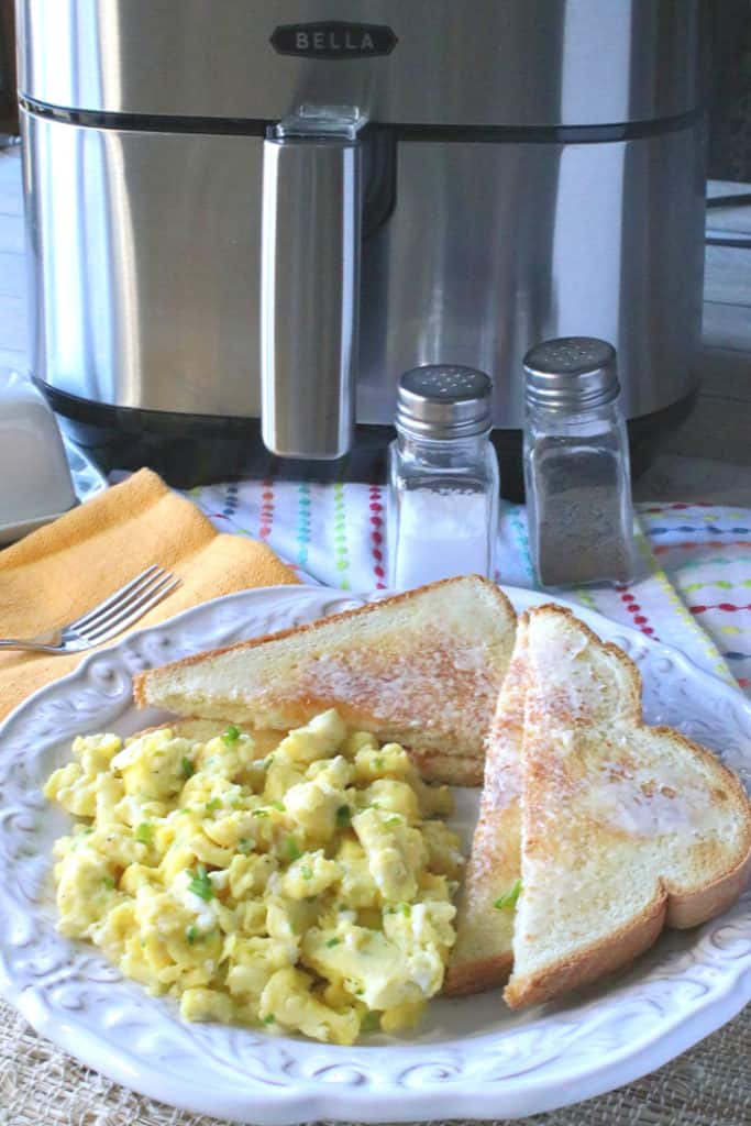 A closeup vertical photo of a plate of scrambled eggs with chives, toast with butter, and an air fryer in the background.