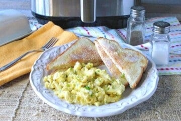 A plate of air fryer scrambled eggs with toast and a salt and pepper shaker in the background.