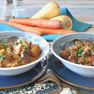 Two bowls of beef stew with carrots and parsnips in the background