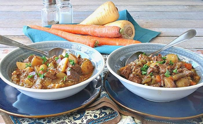 A horizontal photo of two side by side blue bowls filled with beef stew. Each are on a blue plate with spoons and carrots and parsnips are in the background.