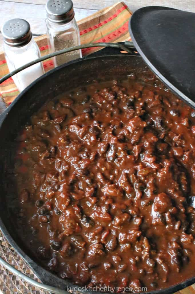 An overhead vertical photo looking inside cast iron a pot of deep, rich, mole turkey chili.