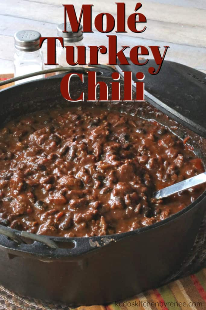 A vertical title text closeup image of a cast iron pot of mole turkey chili with a ladle.
