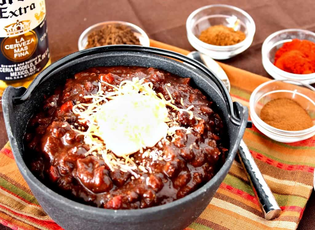 A horizontal photo of turkey chili in a small cast iron pot with small bowls of spices and a spoon in the background.