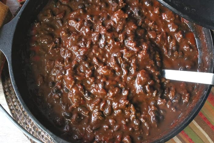 An overhead closeup horizontal photo looking inside a cast iron pot of turkey chili with beans, chorizo, and tomatoes.