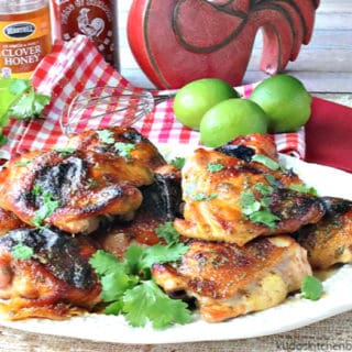 A horizontal photo of a platter of chicken thighs with honey lime sriracha sauce. Fresh limes, cilantro, honey and sriracha sauce is in the background.